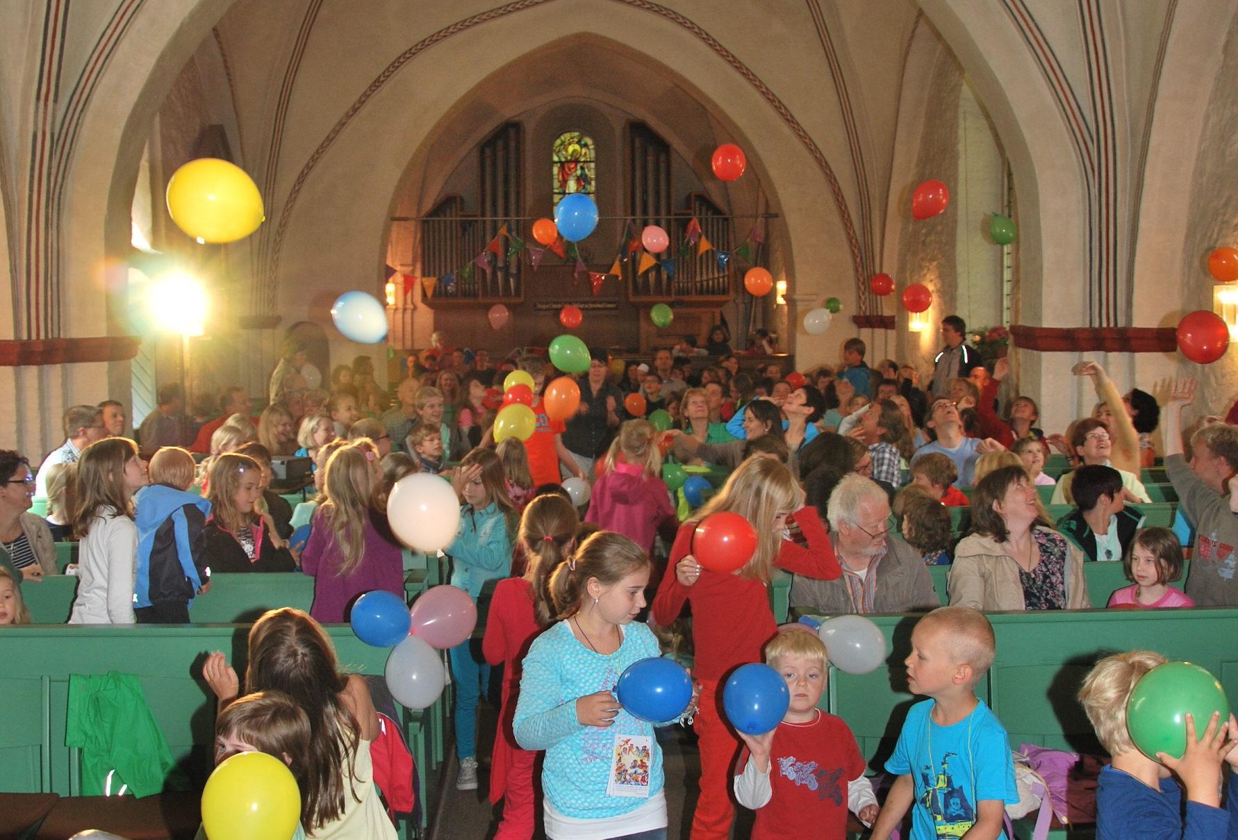 Gottesdienst beim Kinderkirchentag: Die Gemeinde wirft in der vollen Kirche bunte Luftballons in die Luft.
