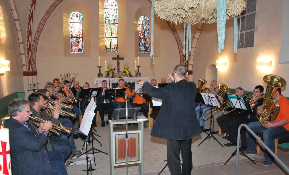 Der Posaunenchor tritt im Altarraum der Kirche zum 65. Jubiläum auf.