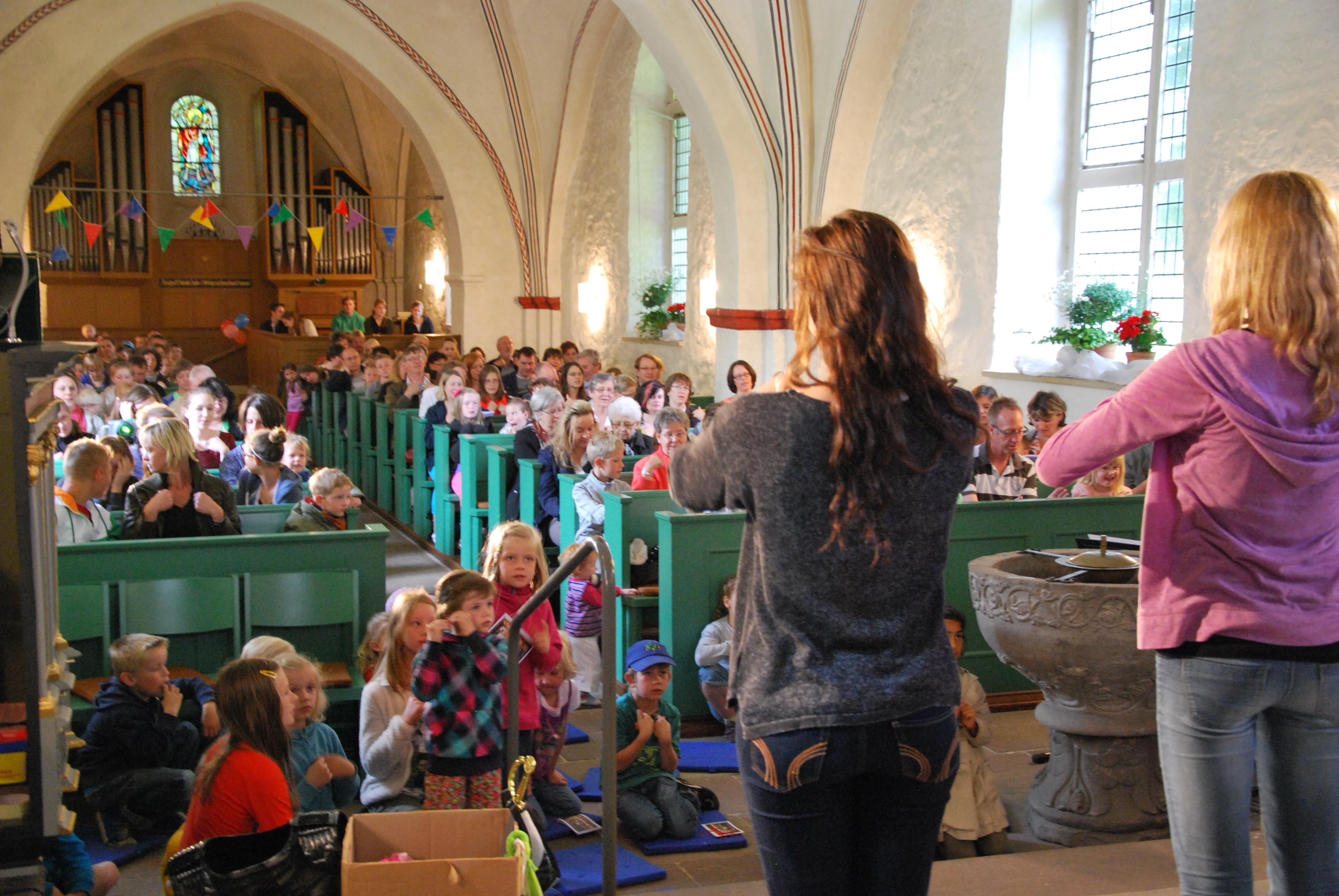 Mitmachlieder beim Kinderkirchentag in der Kirche. Teamer machen Bewegungen für die Gemeinde vor.