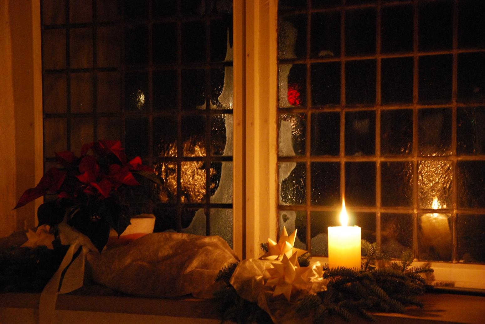 Ein Kirchenfenster zur Adventszeit: Dekoriert mit Adventssternen und Kerzen.
