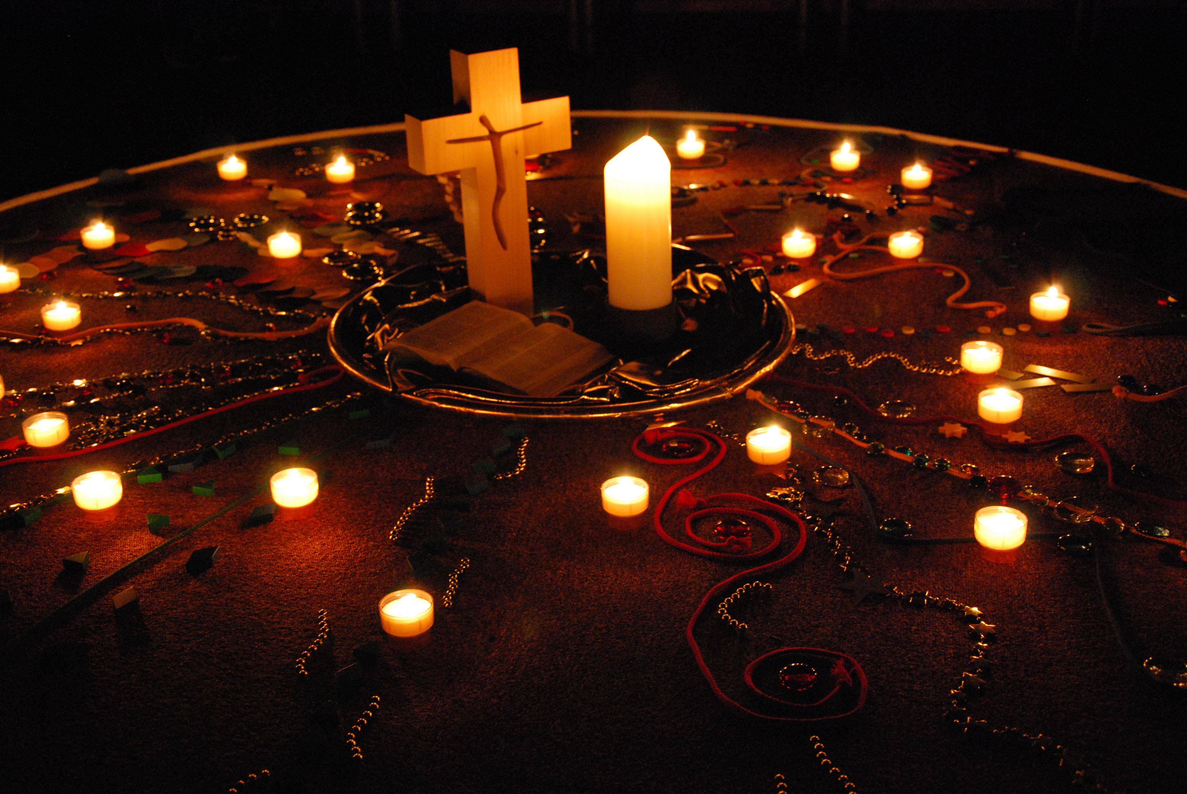 Gestaltete Mitte mit Steinen, Bändern und Kerzen, die zum Kreuz, zur Bibel und zur Kerze in die Mitte führen.