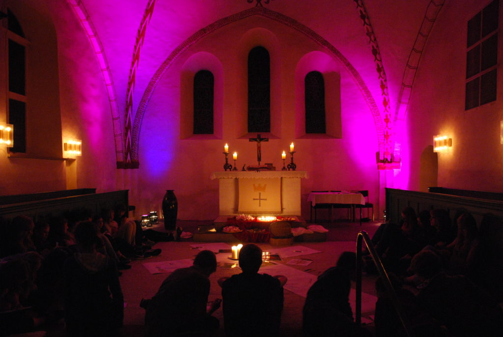 Der Altarraum der Kirche im Dunkeln, erhellt von Kerzen und violetten Lichtern.