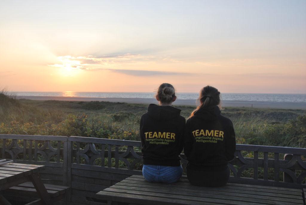 Zwei Teamerinnen der Kirchengemeinde Heiligenfelde sitzen auf einem Tisch und gucken den Sonnenuntergang an.