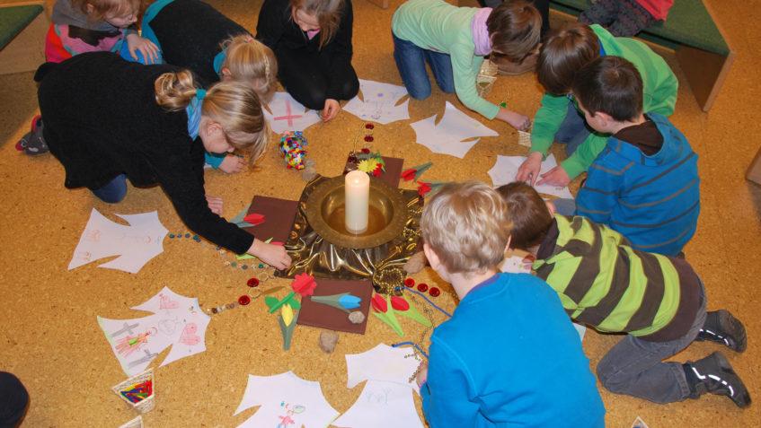 Die Kinder der Kinderkirche legen Bänder und Steine auf den Fußboden zur Mitte mit einer Kerze.