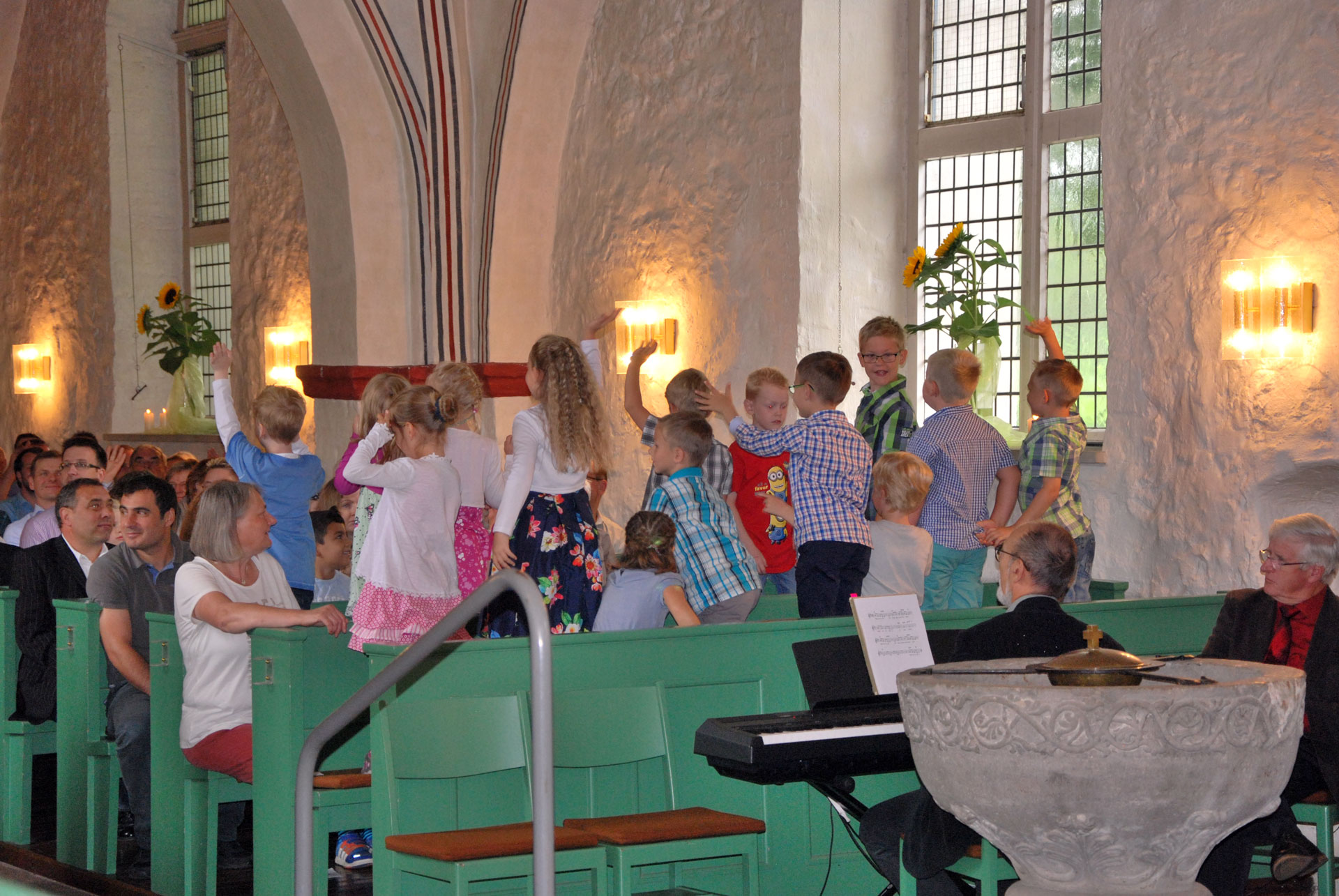 Kinder stehen auf den Kirchenbänken und gucken in die Gemeinde beim Kinderkirchentag.