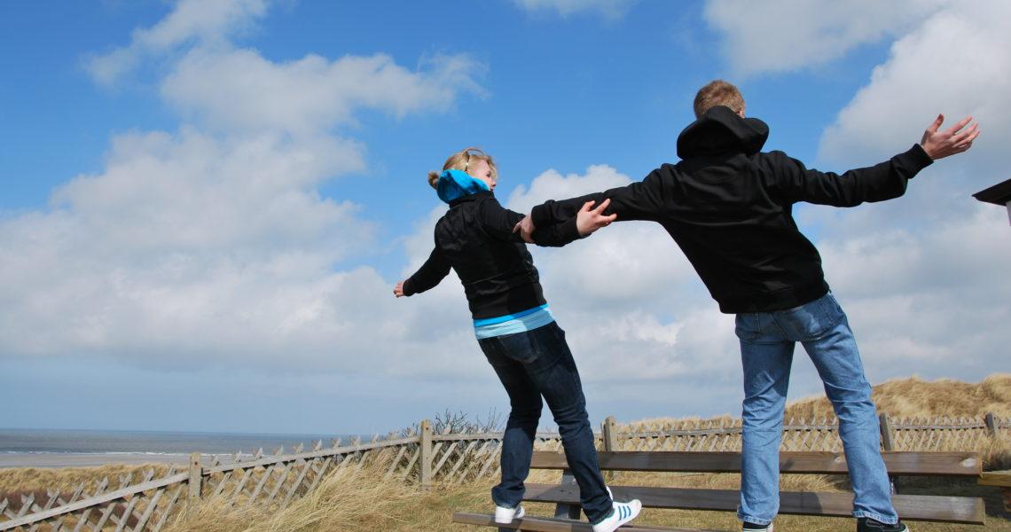 Jugendliche lehnen sich gegen den Wind auf Spiekeroog.