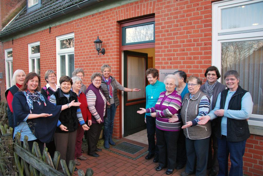 Die Frauen der Frauenhilfe stehen mit offenen Armen vor der geöffneten Tür des Gemeindehauses.