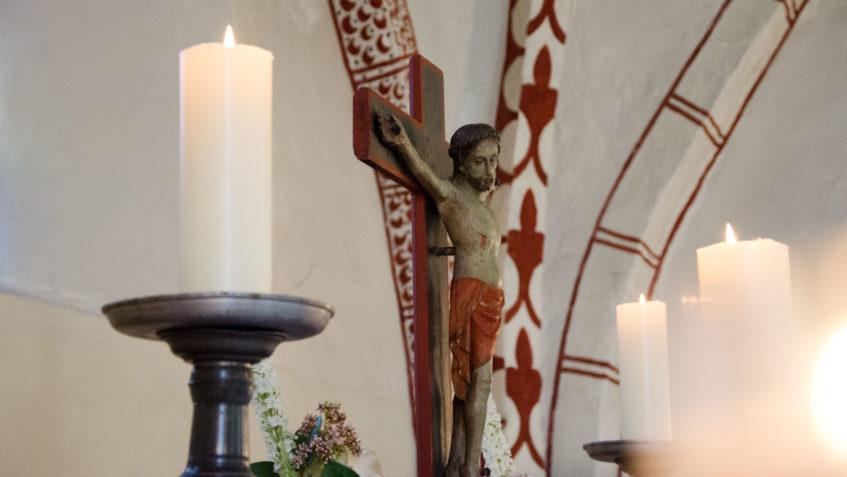 Das Altarkreuz mit Jesus Christus. An den Seiten brennen jeweils Kerzen.