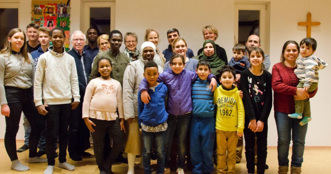 """Flüchtlinge und Ehrenamtliche des Arbeitskreises """"Miteinander-Füreinander"""" auf einem Gruppenbild."""