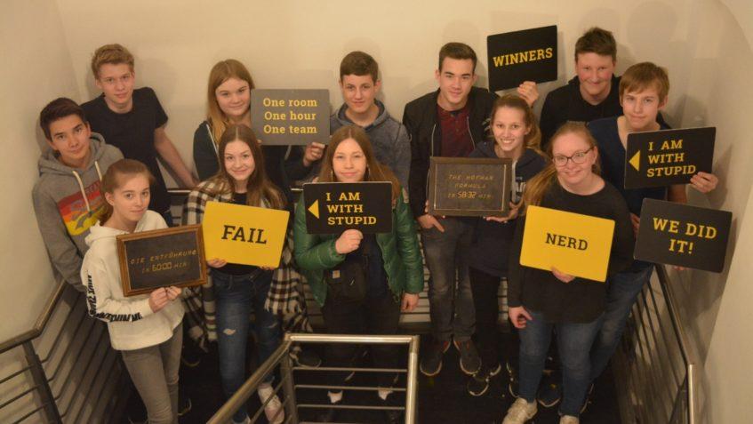 Die Jugendgruppe steht im Treppenhaus des TeamEscape Hamburg mit verschiedenen Schildern.